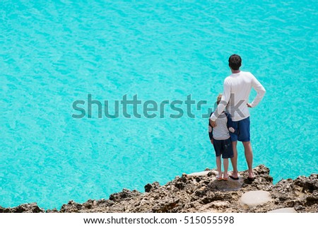 back view of family of two standing at rocky cliff enjoying turquoise caribbean sea, vacation and family concept