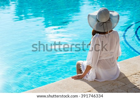 Back view of fashion woman on summer vacation relaxing at luxury resort spa poolside. Young  fashionable lady wearing sun hat and white kaftan. - stock photo
