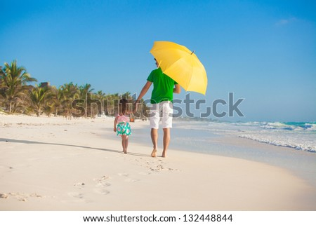 Back view of father and daughter at beach with umbrella to hide from sun - stock photo