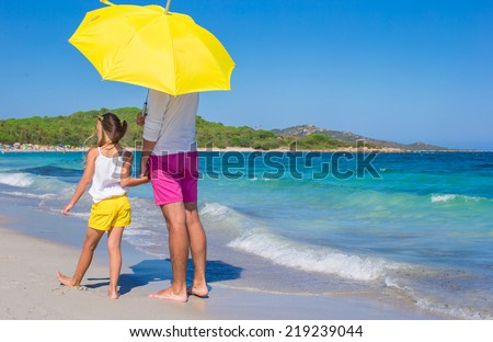 Back view of father and daughter at white beach with yellow umbrella - stock photo
