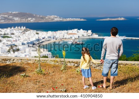 Back view of father and daughter family enjoying views of traditional white village on Mykonos island, Greece