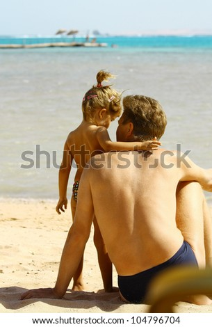 Back view of father and daughter looking to ocean - stock photo