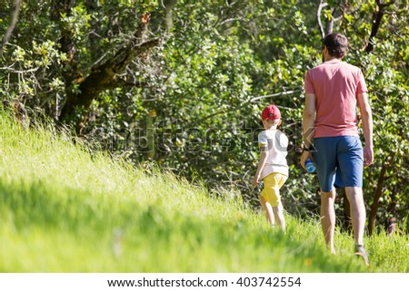 back view of father and his son walking or hiking in the park - stock photo