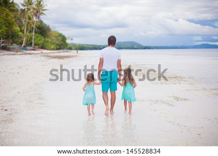 Back view of father and his two little daughters walking by the sea - stock photo