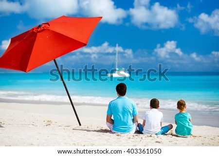 Back view of father and kids enjoying beach vacation - stock photo