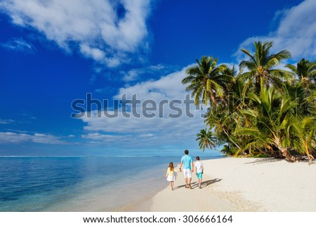 Back view of father and kids walking along tropical beach during summer vacation - stock photo