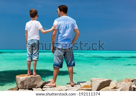 Back view of father and son enjoying views of turquoise ocean water during summer vacation - stock photo