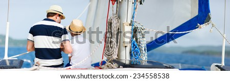 Back view of father and son family sailing on a luxury yacht or catamaran boat - stock photo