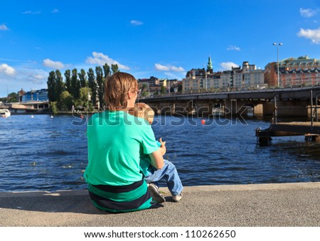 back view of father and son sitting on pier - stock photo