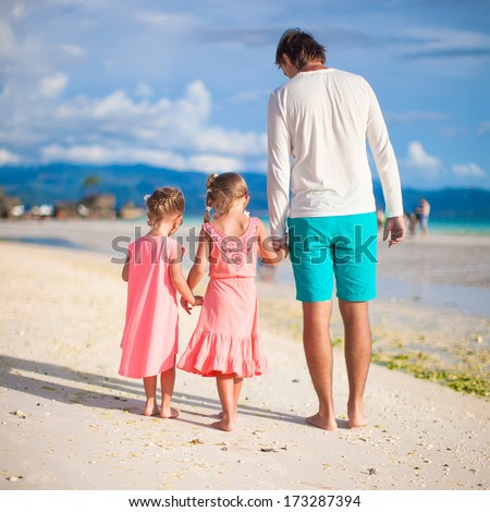 Back view of father and two girls walking on tropical white beach - stock photo