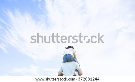 Back view of father carrying his little daughter  - stock photo