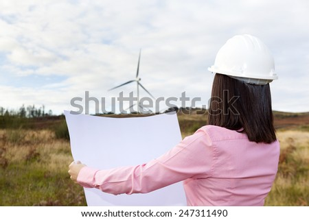 Back view of female engineer holding a blueprint at wind turbine site
