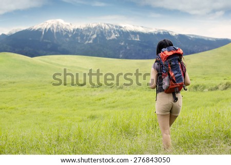 Back view of female hiker walking toward the mountain through the green meadow while carrying a backpack
