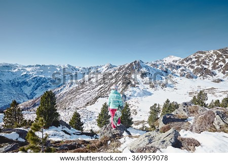 Back view of female snowboarder wearing colorful helmet, blue jacket and pink pants standing with snowboard in one hand and enjoying alpine mountain landscape with no snow - snowboarding concept