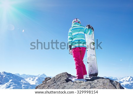 Back view of female snowboarder wearing colorful helmet, blue jacket, grey gloves and pink pants standing with snowboard in one hand and enjoying alpine mountain landscape - winter sports concept - stock photo