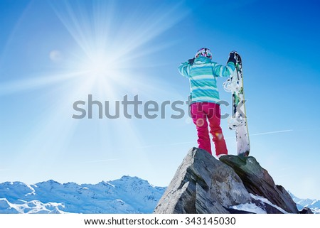 Back view of female snowboarder wearing helmet, blue jacket, gloves and pink pants standing with snowboard and looking at sunny alpine mountain landscape covering her eyes - winter sports concept - stock photo