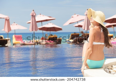 back view of fit woman in straw hat by luxury spa pool - stock photo