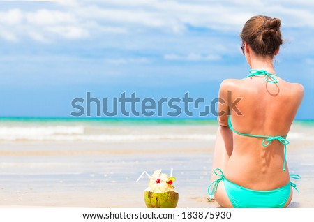 back view of fit young woman in bikini with coconut on the beach - stock photo