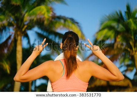 Back view of fitness woman doing success victory gesture after beach vacation workout. Motivation and exercising success concept.