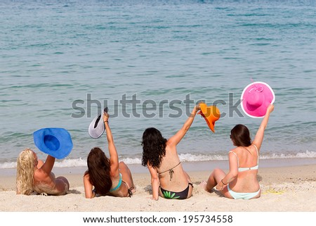 Back View of four young playful women in summer hats resting on the beach and enjoy the tropical sea.