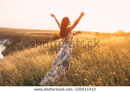 Back view of free Happy Woman Enjoying summer outdoors at Nature with sunlight. Freedom concept in meadow