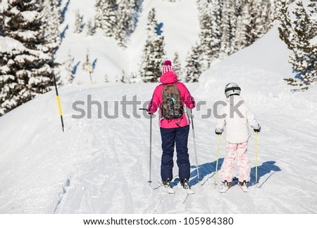 Back view of girl in ski goggles and a helmet with his mother, Zellertal, Austria. Vertical view - stock photo