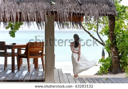back view of girl watching towards the sea in beach pavilion - stock photo