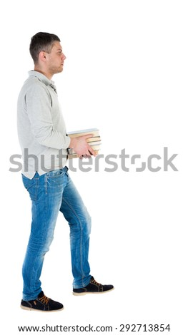 Back view of going  handsome man carries a stack of books. walking young guy . Rear view people collection.   Isolated over white background. A guy in a white jacket comes with a stack of books. - stock photo