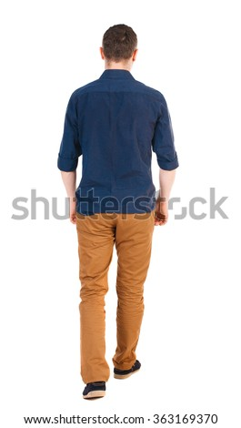Back view of going  handsome man in jeans and a shirt.  walking young guy .  Isolated over white background.  man in brown pants, shirt sleeves rolled away into the distance. - stock photo