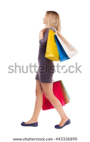 back view of going  woman  with shopping bags. beautiful girl in motion.  backside view of person. Rear view people collection. Isolated over white. Girl in dress is right throwing shoulder paper bags - stock photo