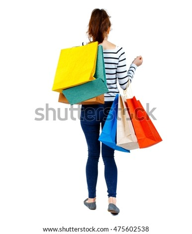 back view of going woman with shopping bags . beautiful girl in motion. Girl in a striped sweater went off with his shopping bags on her shoulder.