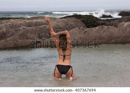 back view of gorgeous tattooed bikini model kneeling in the sea with her arms outstretched with copyspace - stock photo