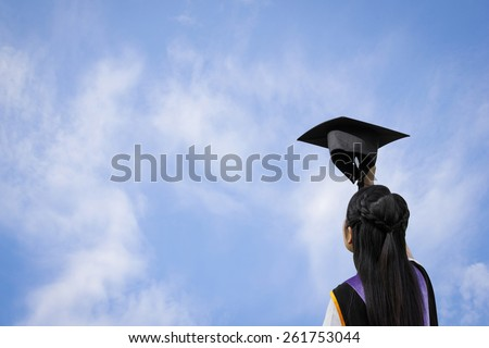 Back view of graduate student girl with hand holding hat up to the sky. - stock photo