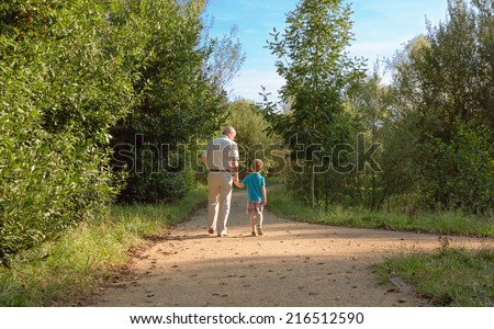 Back view of grandfather and grandchild walking on a nature path - stock photo