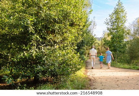 Back view of grandparents and grandchild walking on a nature path - stock photo