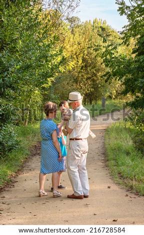 Back view of grandparents and grandchildren having fun on nature - stock photo