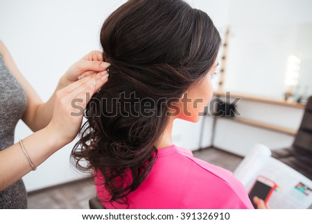 Back view of hairstyle of young woman with curly dark hair made by female hair stylist in beauty salon - stock photo