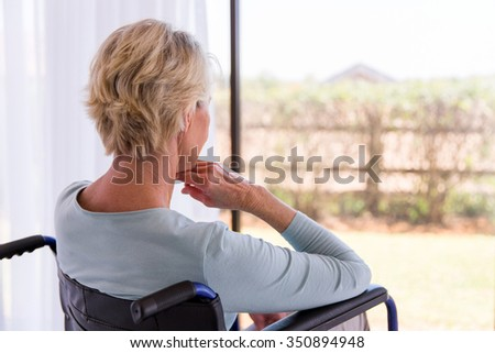 back view of handicapped senior woman looking through window - stock photo