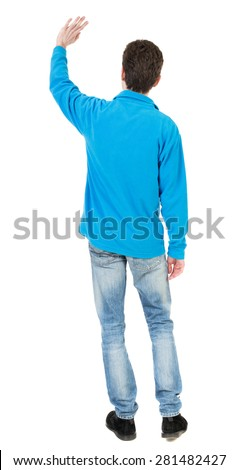 Back view of handsome man greeting waving from his hands. Standing young guy in jeans. backside view of person.  Isolated over white background.  The guy in the blue sweater waving his left hand