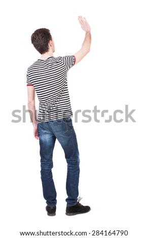 Back view of handsome man greeting waving from his hands. Standing young guy in jeans. Rear view people collection.  backside view of person.  Isolated over white background. Curly French waves. - stock photo