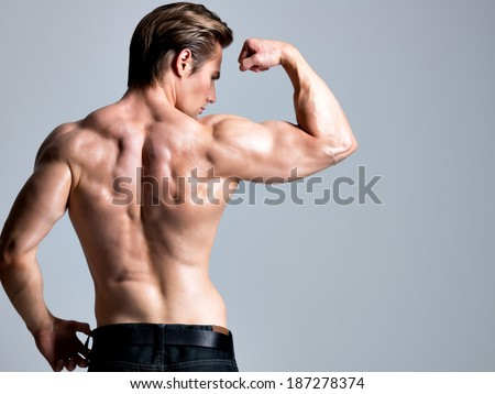 Back view of handsome man with sexy muscular beautiful body posing at studio. - stock photo