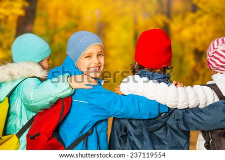 Back view of happy children with rucksacks - stock photo