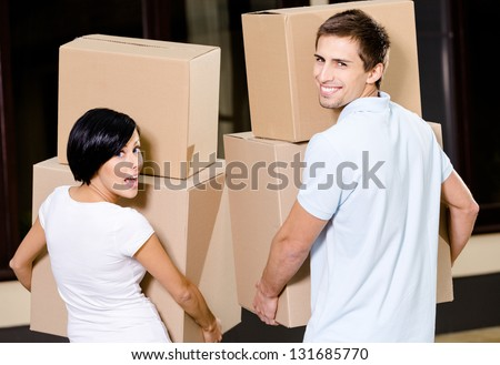 Back view of happy couple carrying pasteboard packages while moving to new house - stock photo