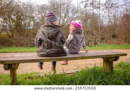Back view of happy cute boy and little girl talking and playing sitting on a wooden bench in the park - stock photo
