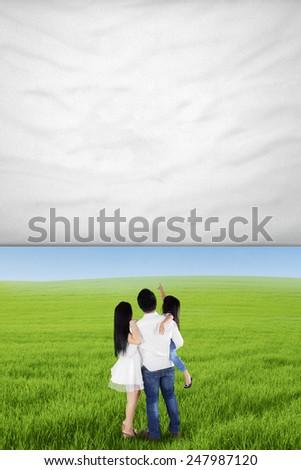 Back view of happy family standing on the meadow while looking at empty banner - stock photo