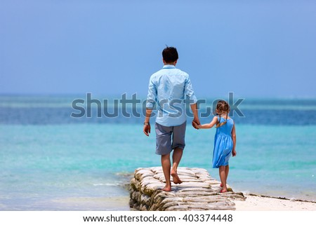 Back view of happy father and his adorable little daughter at tropical beach during summer vacation - stock photo