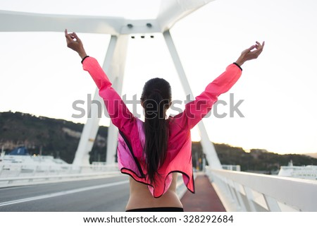 Back view of happy female with slender figure standing on a city bridge with raised hands while enjoying beautiful day after training, young sporty woman dressed in tracksuit relaxing after workout - stock photo