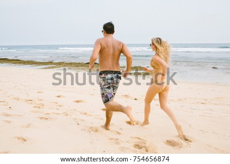 Back view of happy joyful young couple running on the beach