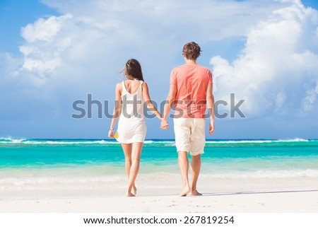 back view of happy romantic young couple on the beach - stock photo
