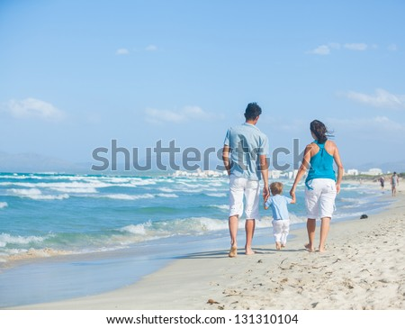 Back view of happy young family - mother, father and son having fun on the beach